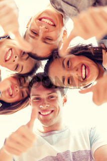 group of smiling teenagers looking down