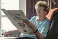 An old lady sitting in her chair by the window, re