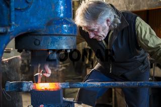 Schmied arbeitet am Elektrohammer