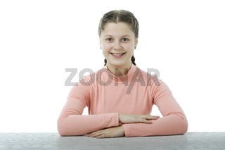 Little girl at the table in school isolated on white
