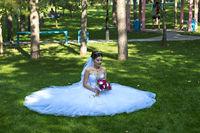 Braut sitzt mit ausgebreitetem Hochzeitskleid auf dem rasen in einem Park