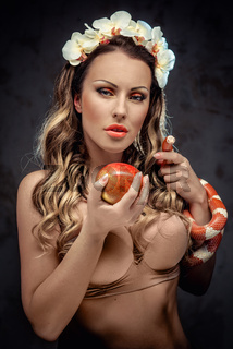 Sexy beautiful woman with red apple and snake, conceptual photo