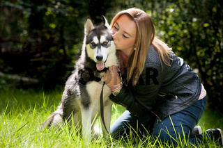 Girl is sitting with her dog in the grass