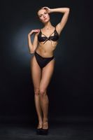 Beautifu woman in black lingerie posing in studio.