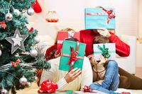 Familie hält Geschenke vor die Gesichter zu Weihnachten
