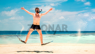 Funny man jumping in flippers and mask.