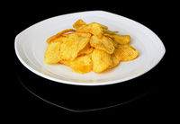Potato chips on a plate on a black background