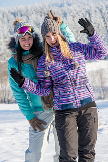 Two girlfriends in winter snow mountains smiling