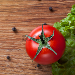 red tomato with green salad on wood