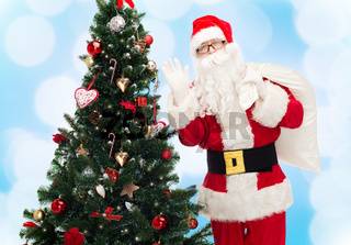 santa claus with bag and christmas tree