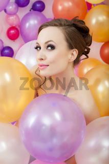 Portrait of flirty brunette posing with balloons