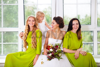Cheerful bride with female friends and little flower girl