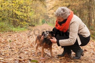 Middle ager is taking care of her dog