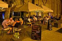 Touristen sitzen am Abend in einem open-air Restaurant an der St. John's Co-Cathedral