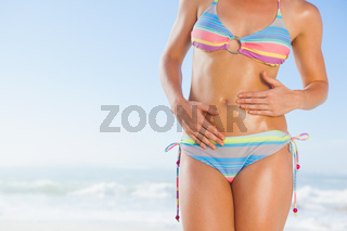 Mid section of fit woman in bikini on the beach