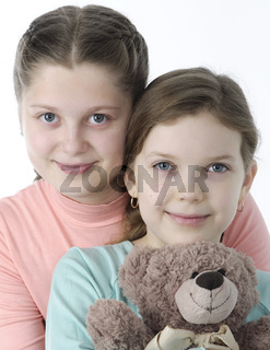 Portrait of pretty little girls holding teddy bear isolated on white