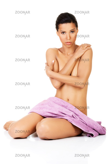 Attractive naked woman sitting covered with towel. Front view.