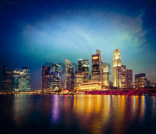 Vintage retro hipster style travel image of Singapore skyline and Marina Bay in evening