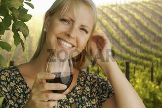 Attractive Woman Enjoying a Glass of Wine at the Vineyard