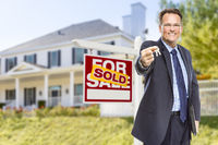 Agent with Keys in Front of Sold Sign and House