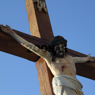 Holy cross with crucified Jesus Christ against a background of blue sky