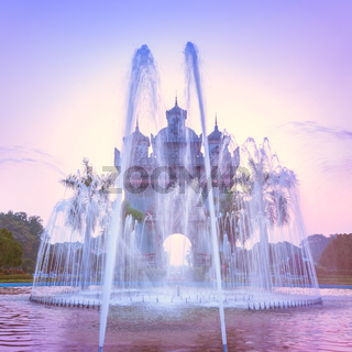 Sunset view of Patuxai arch or Victory Triumph Gate monument with fountain in front.  Vientiane, Laos travel landscape and destinations