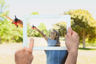 Composite image of hand holding tablet pc