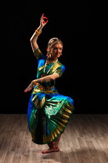 Young beautiful woman dancer exponent of Indian classical dance Bharatanatyam in Shiva pose