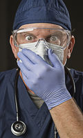Stunned Doctor or Nurse with Protective Wear and Stethoscope