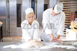 Baker instruction apprentice in kneading bread dough