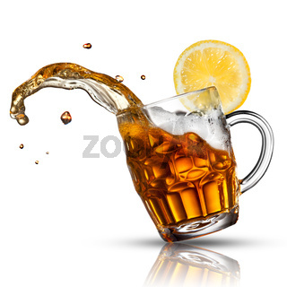 Beer splash in glass with lemon isolated on white