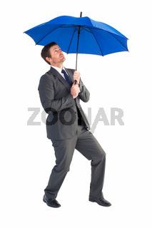 Businessman sheltering under blue umbrella