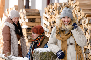 Young people outside winter cottage wooden logs