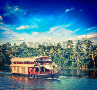 Vintage retro hipster style travel image of Kerala travel tourism background - houseboat on Kerala backwaters. Kerala