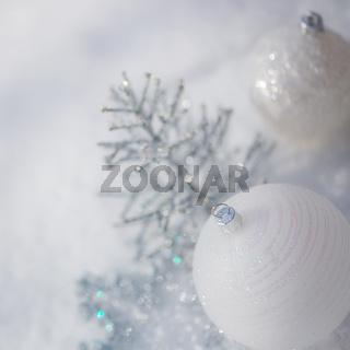 Silver Christmas tree decorations on snow