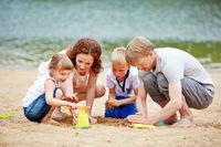 Familie baut Sandburg im Urlaub