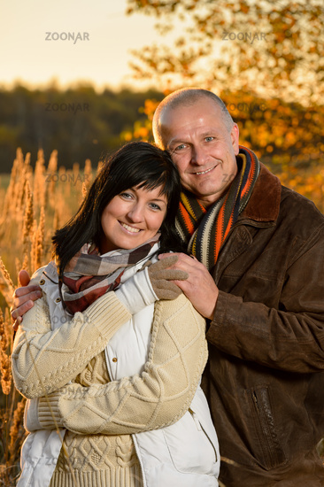 Romantic couple embracing in autumn sunset park