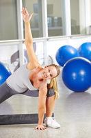 Frau macht Gymnastik im Fitnesscenter
