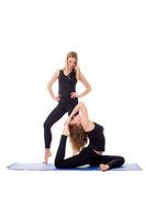 Cute girlfriends exercising on fitness mat
