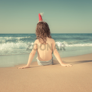Child in Santa hat at the beach
