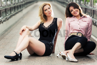 Two happy young women sitting on the sidewalk