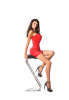 Elegant beautiful woman sitting on a contemporary metal bar stool, isolated on white