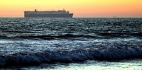 Sunset at a beach with cargo ship in the background.