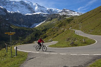 Biker pedaling through a hairpin bend,Switzerland