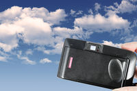 An old used film plastic camera over blue sky with