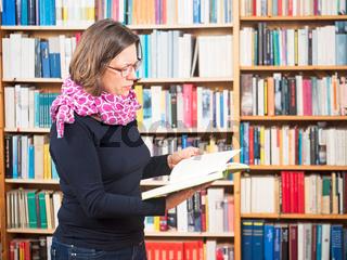 Frau mit Buch vor Bücherregal