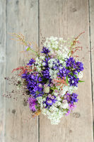 Beautiful tender bouquet of summer meadow flowers on wooden background. Floral composition in rural vintage style