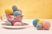 Brightly colored eggs in tea cup on yellow backgro