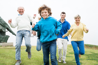 Happy family running at the lawn