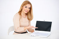 Sitting Smiling Woman Showing Laptop on Table